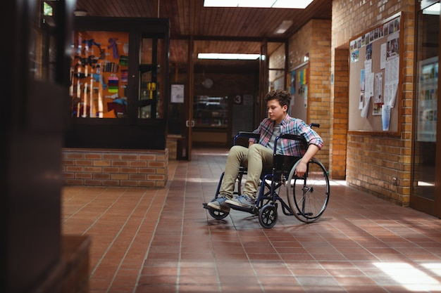Школьник-инвалид на инвалидной коляске в коридоре в школе