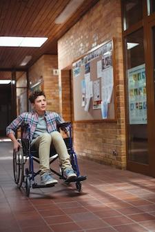 Школьник-инвалид на инвалидной коляске в коридоре