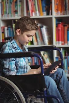 Школьник-инвалид с помощью цифрового планшета в библиотеке