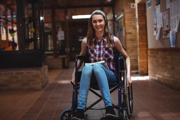 Школьница-инвалид на инвалидной коляске в коридоре в школе