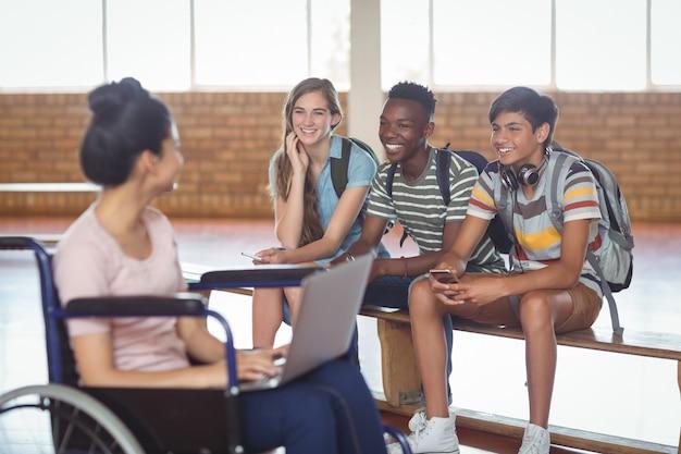 Школьница-инвалид с одноклассниками во время использования ноутбука в кампусе