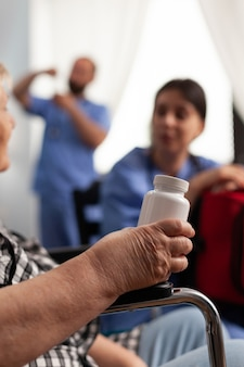 Disabled senior elderly patient holding vial of pills discussing disease therapy