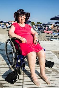 Инвалид старшей женщины на пляж благодаря специальной инвалидной коляске