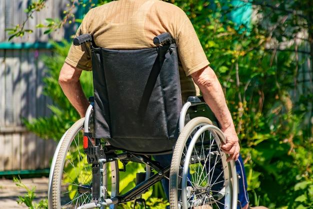 田舎のコテージ、高齢者の病気の椅子に障害者の年配の男性