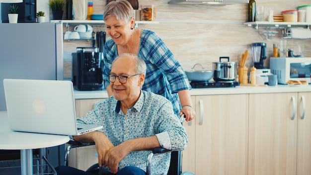 車椅子の障害者の年配の男性と彼の妻が台所のラップトップでビデオ会議を行っています。オンライン会議を行っている麻痺した老人と彼の妻。