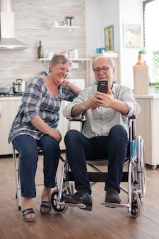 車椅子の障害者の年配の男性と彼の妻は、キッチンで現代のスマートフォンで笑ったりブラウジングしたりします。オンライン会議をしている麻痺した老人と彼の妻。