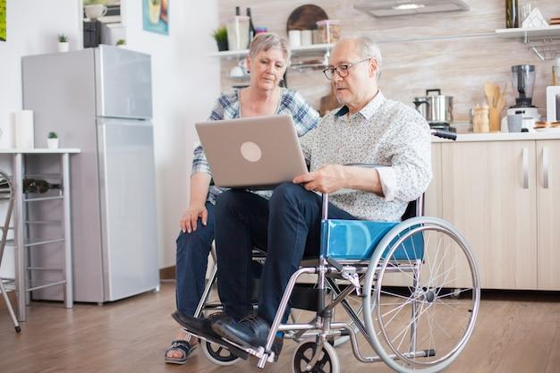 車椅子の障害者の年配の男性と彼の妻は、キッチンのタブレットpcでビデオ会議を介して家族と話しています。オンライン会議をしている麻痺した老人と彼の妻。