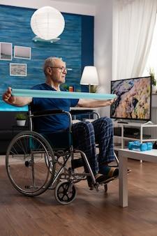 身体のトレーニングを行うゴムバンドで車椅子トレーニング中の障害者の年配の男性