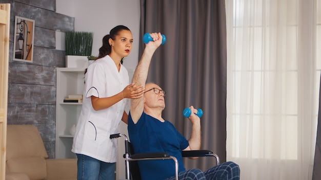 Disabled senior man in wheelchair doing physiotherapist with support from therapist. disabled handicapped old person with social worker in recovery support therapy physiotherapy healthcare system nurs