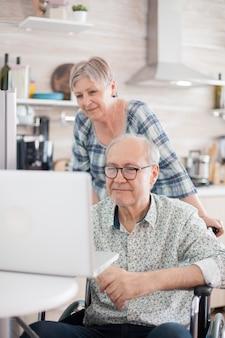 Uomo anziano disabile in sedia a rotelle e sua moglie che hanno una videoconferenza sul computer portatile in cucina. un vecchio paralizzato e sua moglie hanno una conferenza online.