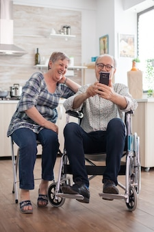 Uomo anziano disabile in sedia a rotelle e sua moglie che ridono e navigano con un moderno smartphone in cucina. un vecchio paralizzato e sua moglie hanno una conferenza online.