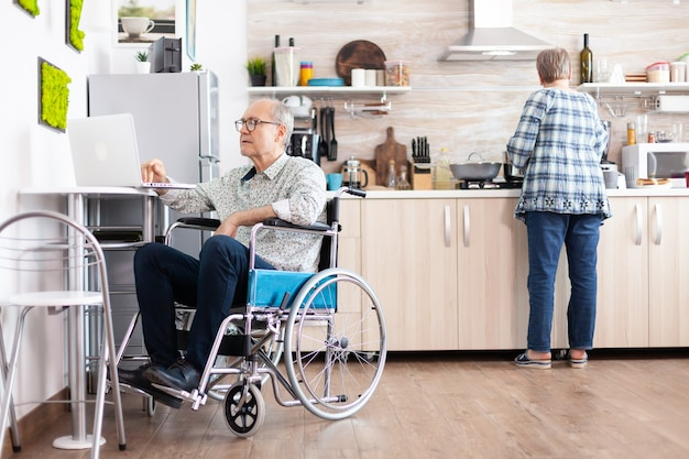 Disabled senior man in wheelchair working from home at laptop in kitchen while wife is cooking breakfast. handicapped businessman, disabilty entrepreneur paralysis for elderly retired man.