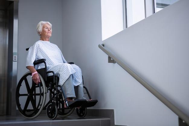 階段の近くの車椅子の障害のあるシニア患者