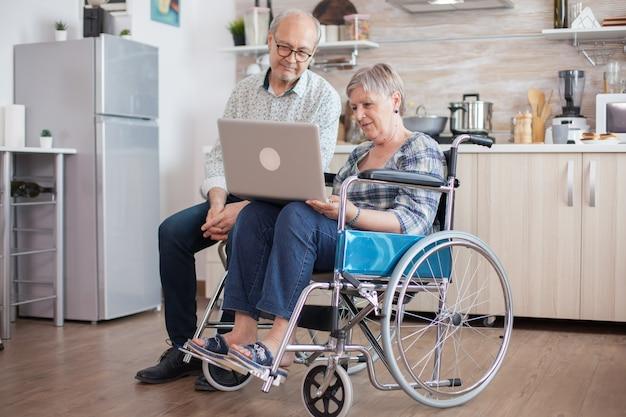 휠체어를 탄 장애인 노인과 남편이 부엌에서 태블릿 pc로 화상 회의를 하고 있습니다. 마비된 노부와 그녀의 남편이 온라인 회의를 하고 있습니다.