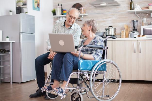 車椅子の障害者の年配の女性と彼女の夫がキッチンのタブレットpcでビデオ会議を行っています。オンライン会議をしている麻痺した老婆と彼女の夫。