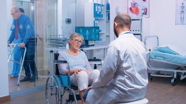 휠체어를 탄 장애인 노인 여성은 현대적인 개인 병원이나 병원의 의사에게 의료 상담을 받고 있습니다. 회복 치료, 장애인을 위한 도움. 노인 지원