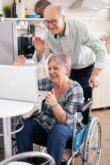 夫の隣に座っているビデオ会議中に手を振っている車椅子の障害者の年配の女性。現代の通信技術を使用して、オンライン通話で麻痺した障害のある老婆と彼女の夫。