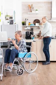 휠체어를 탄 장애인 노인 여성은 부엌에서 노트북으로 집에서 일하고 남편은 아침을 준비합니다. 장애인 사업가, 은퇴한 노년 여성을 위한 장애인 사업가