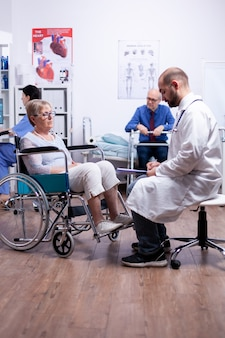 Disabled senior woman sittinf in wheelchair during medical consultation in recovery clinic