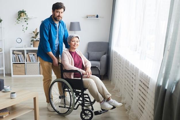 장애인 수석 여자 휠체어에 앉아 남자가 그녀의 뒤에 서있는 카메라에 웃고 그들은 집에서 방에 있습니다