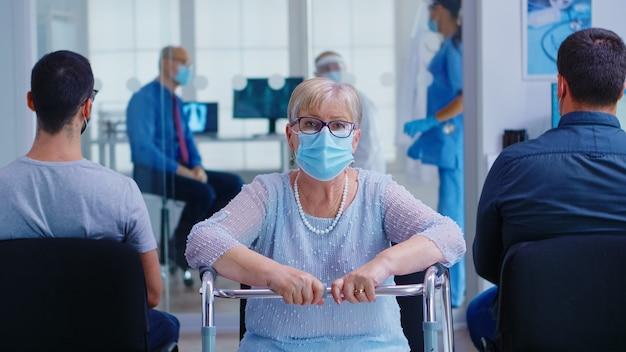 Donna anziana disabile con maschera facciale contro il coronavirus e deambulatore che guarda la telecamera nell'area di attesa dell'ospedale. infermiera che assiste il medico durante la consultazione nella sala d'esame.
