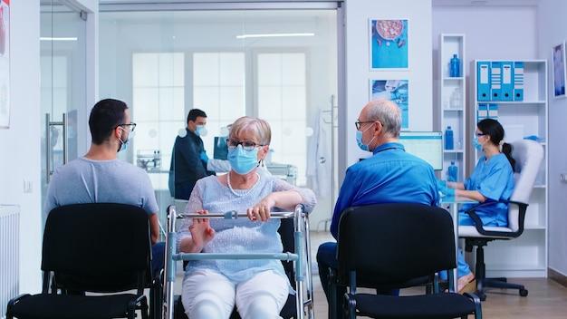 Старшая женщина-инвалид с прогулочной рамой в зоне ожидания больницы в маске для лица от коронавируса. пациенты ждут обследования в коридоре больницы.