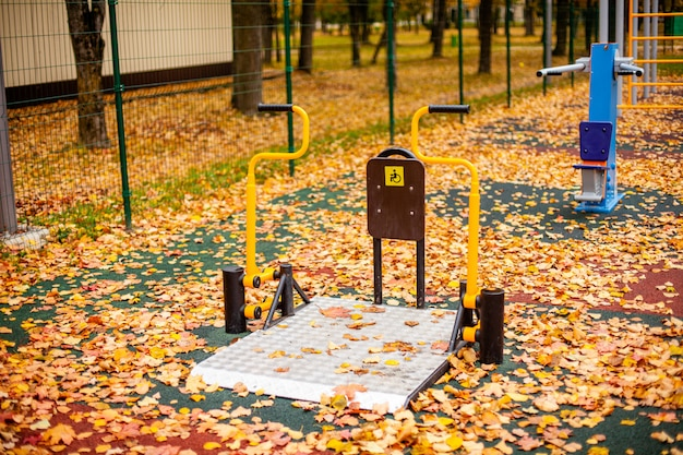 Disabled simulator in the autumn park. yellow autumn leaves lie on the playground.