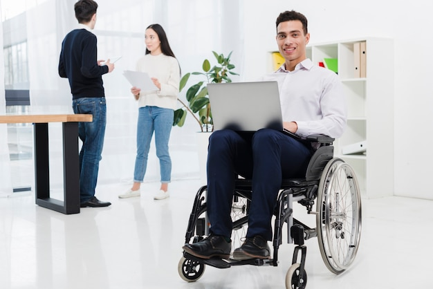 A disabled smiling young businessman sitting on wheelchair with laptop in front of business colleague