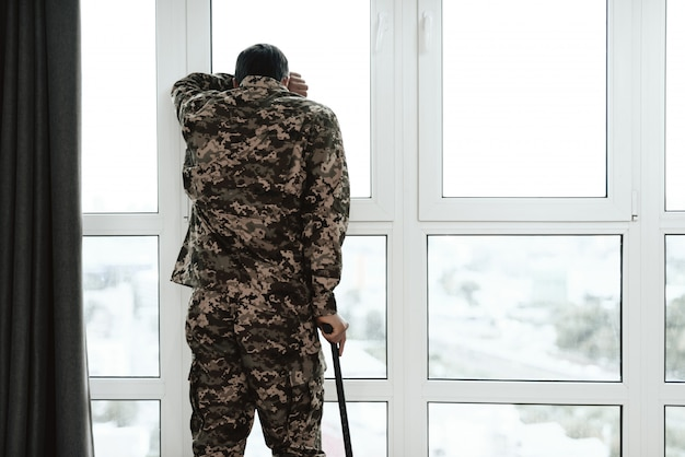 A disabled soldier stands with his hand on the window