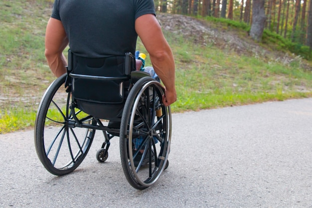 Disabled sports man on a wheelchair in a park