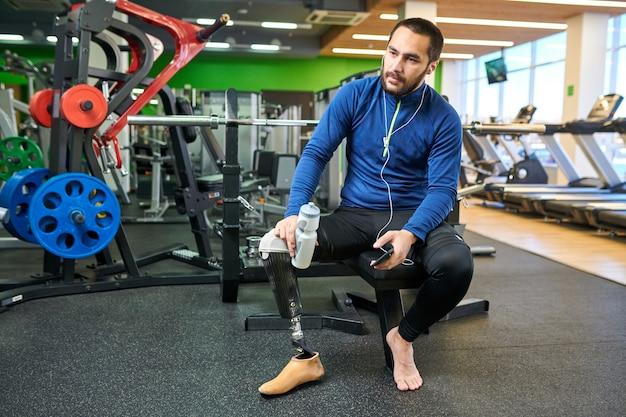 Спортсмен с ограниченными возможностями отдыхает в спортзале