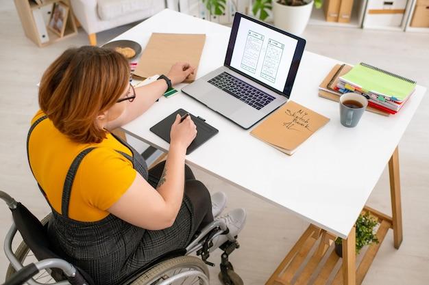 Дизайнер пользовательского интерфейса с ограниченными возможностями сидит в инвалидной коляске и просматривает эскиз на ноутбуке