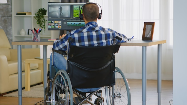 Disabled video editor sitting on wheelchair doing post production on film.