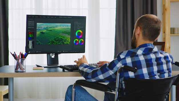 Disabled videographer in wheelchair working from home office.