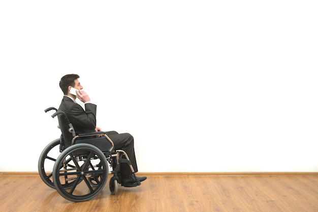 The disabled in a wheelchair phones on the white wall background