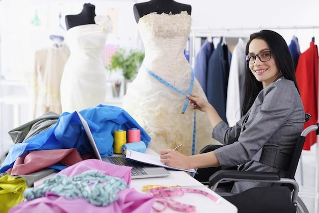 障害のある女性デザイナーは、ウェディングドレスを縫うためのサービスを提供しています。人々のための職業