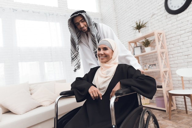 A disabled woman in a hijab is sitting in a wheelchair.