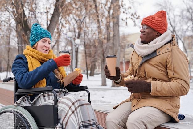 Женщина-инвалид в инвалидной коляске пьет горячий чай с африканским мужчиной в зимний день на открытом воздухе