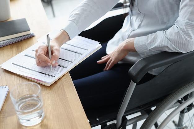 고용 근접 촬영을위한 신청서를 작성하는 휠체어 장애인 여성