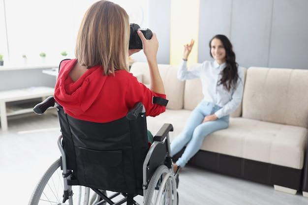휠체어를 탄 장애인 여성이 집에서 모델을 촬영합니다. 삶의 개념을 이행하는 장애인을 위한 일