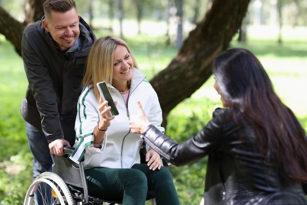 車椅子の障害のある女性は、友人に仕事の財務指標を備えたスマートフォンを示しています