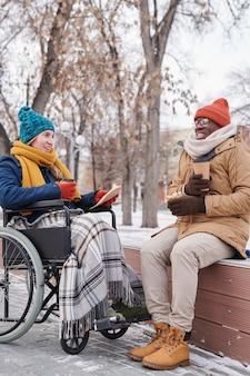 휠체어를 탄 장애인 여성은 공원에서 산책하는 동안 친구와 이야기하고 뜨거운 차를 마신다