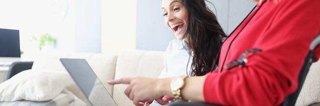 ラップトップを膝に抱えた車椅子の障害のある女性は、彼女の楽しいガールフレンドに彼女の業績を示しています...