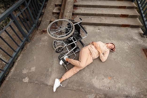 A disabled woman lies on the ground near the stairs near the wheelchair. the concept of a wheelchair, disabled person, full life, paralyzed, disabled person.