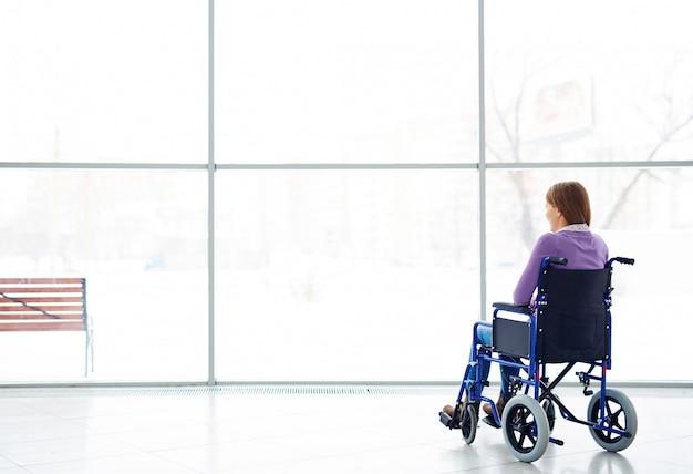 Женщина-инвалид смотрит в окно
