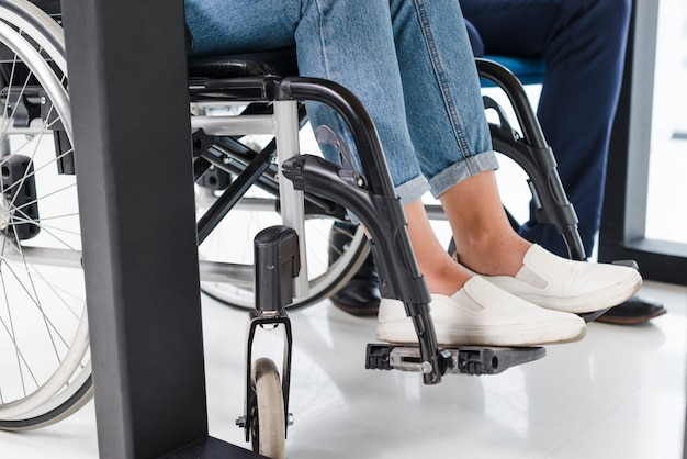 Disabled woman's feet on wheel chair on white floor