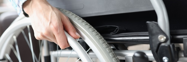 Disabled woman sitting in wheelchair and holding on to wheel closeup