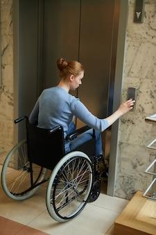 Женщина-инвалид с помощью лифта