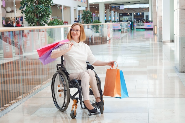 A disabled woman wearing a santa hat, enjoying a christmas sale in a shopping mall