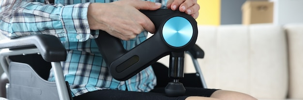 Disabled woman in wheelchair doing leg massage with percussion massager closeup